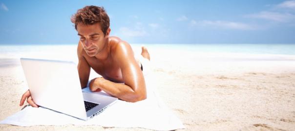 Человек работает на берегу океана с ноутом